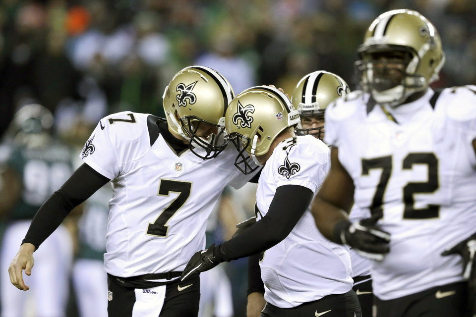 Photo - New Orleans Saints' Luke McCown (7) celebrates with Shayne Graham (3) after Graham's field goal during the first half of an NFL wild-card playoff football game against Philadelphia Eagles, Saturday, Jan. 4, 2014, in Philadelphia. (AP Photo/Julio Cortez)