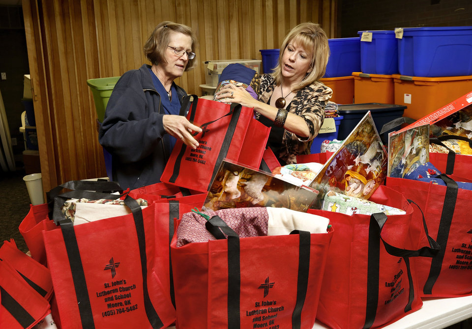 Photo - Volunteers Paulette Owens and Beth Groh insert hand-made quilts into bags filled with Christmas items to be given to families affected by the May 19 and 20 tornados as part of the CHRISTMAS Cares Moore outreach at St. John's Lutheran Church in Moore.   Jim Beckel - THE OKLAHOMAN