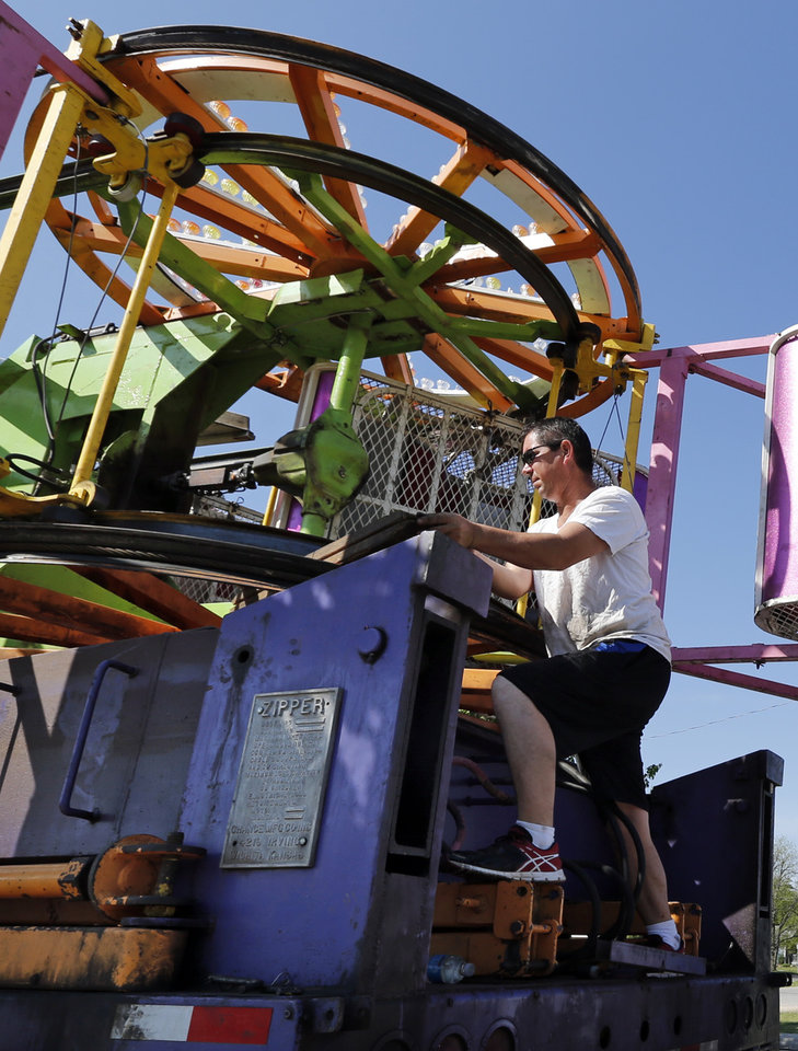 Photo -  Robert Lujan, co-owner of Great Plains Amusements from Rush Springs, sets up the Zipper ride for the annual Lions Club Carnival in downtown Norman. The carnival opens at 5 p.m. Thursday. PHOTO BY STEVE SISNEY, THE OKLAHOMAN   STEVE SISNEY -
