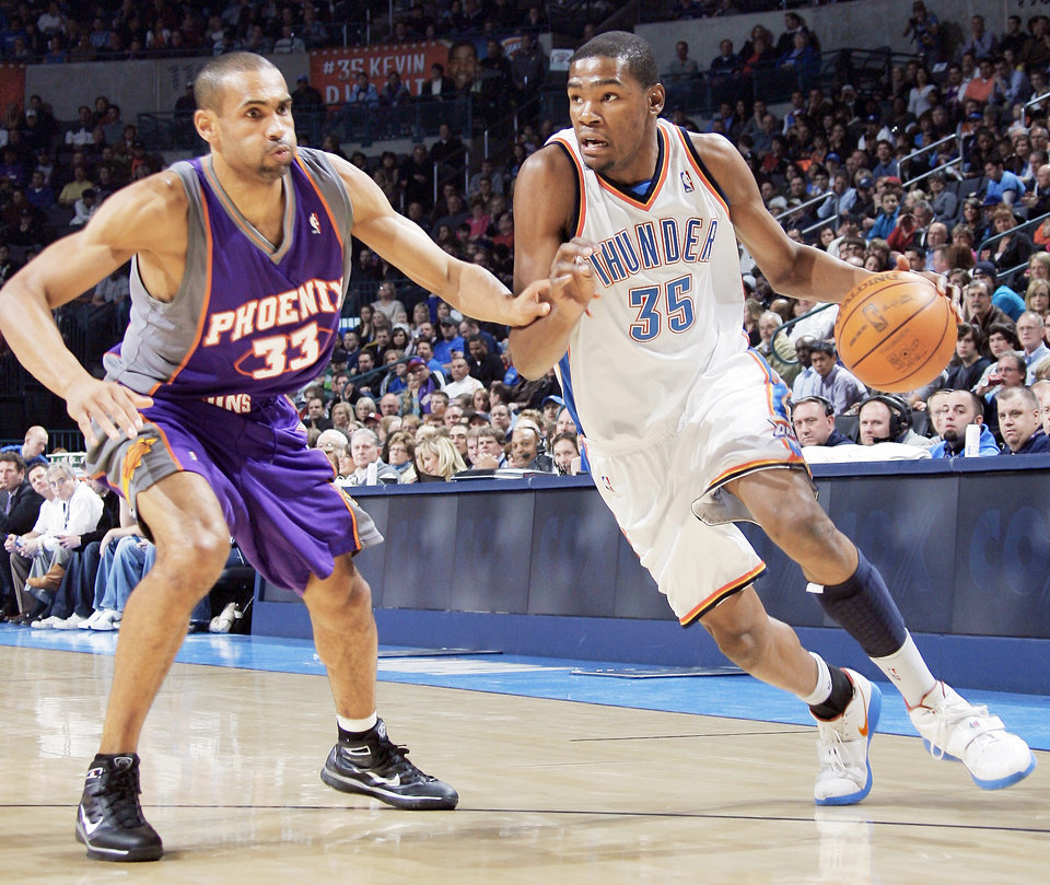 Photo - Thunder forward Kevin Durant, right, drives past Phoenix's Grant Hill during Oklahoma City's loss on Feb. 23 at the Ford Center. PHOTO BY NATE BILLINGS, THE OKLAHOMAN