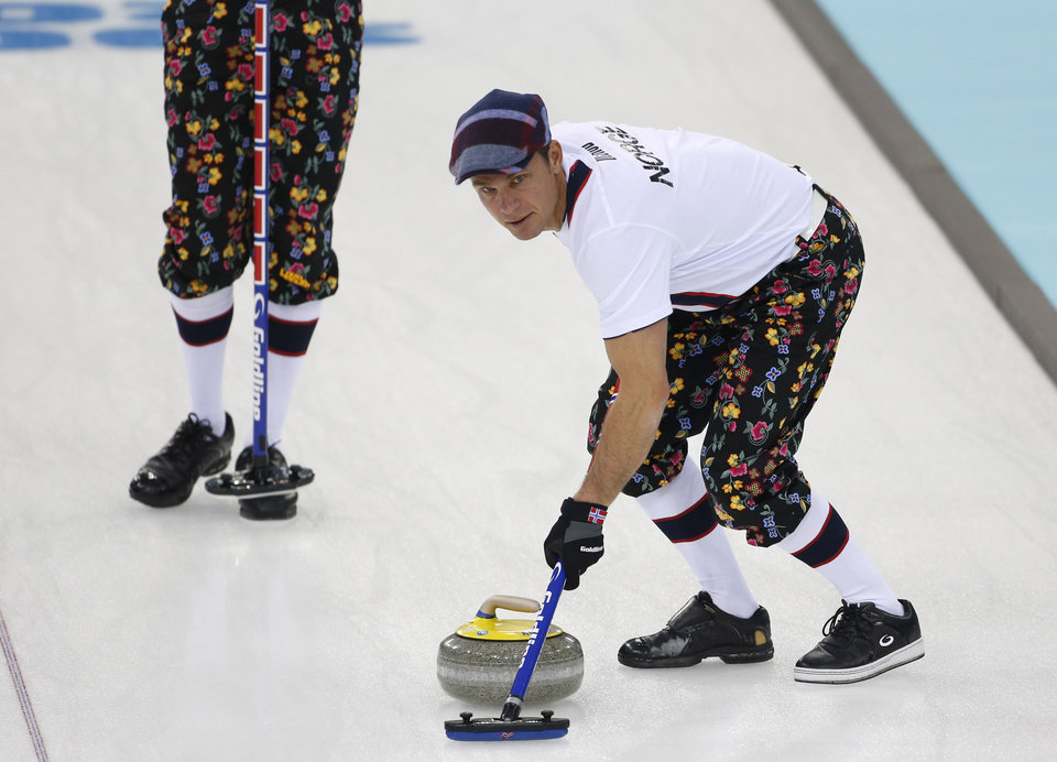 Photo - Norway skip Thomas Ulsrud, wearing rose-painting knickers and a patterned flat cap, sweeps ahead of the stone during curling training at the 2014 Winter Olympics, Saturday, Feb. 8, 2014, in Sochi, Russia. (AP Photo/Robert F. Bukaty)
