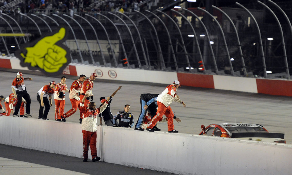 Photo - Crew members climb on top of the pit-road wall to congratulate Kevin Harvick after he won the NASCAR Sprint Cup auto race at Darlington Raceway in Darlington, S.C., Saturday, April 12, 2014. (AP Photo/Mike McCarn)