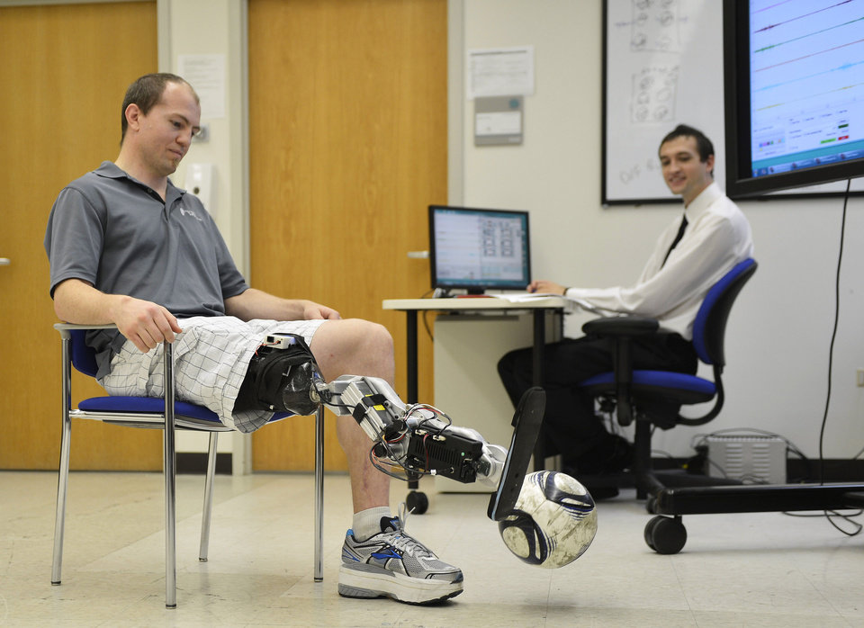 "In this Oct. 25, 2012 photo, Zac Vawter kicks a soccer ball with an experimental ""bionic"" leg as biomedical student Aaron Young makes adjustments to the leg at the Rehabilitation Institute of Chicago. After losing his right leg in a motorcycle accident, the 31-year-old software engineer signed up to become a research subject, helping test a trailblazing prosthetic leg that's controlled by his thoughts. He will put this leg to the ultimate test Sunday, Nov. 4 when he attempts to climb 103 flights of stairs to the top of Chicago's Willis Tower, one of the world�s tallest skyscrapers. (AP Photo/Brian Kersey)"