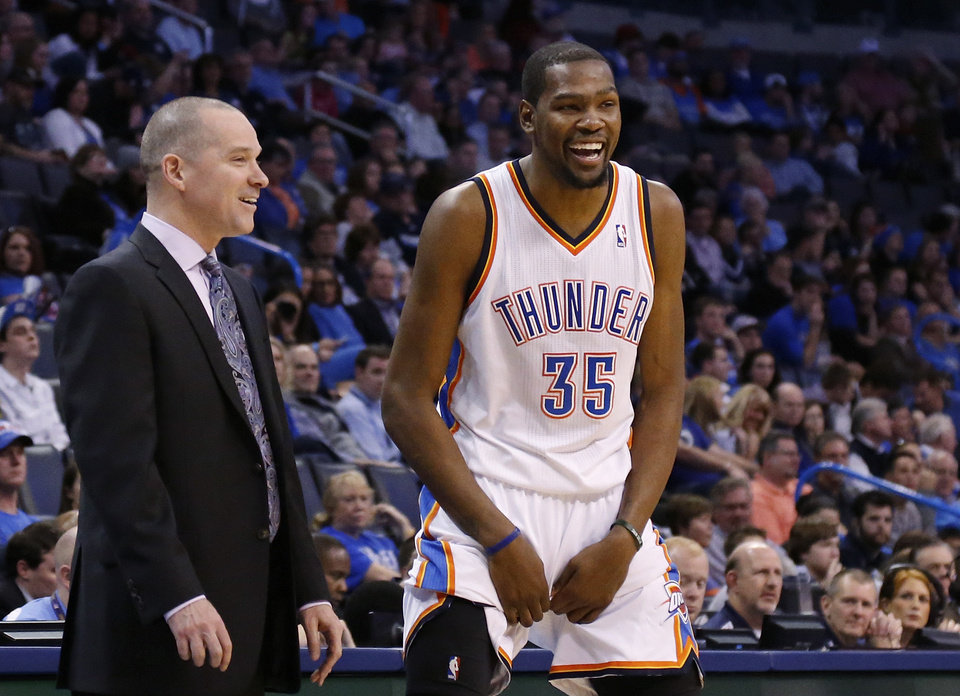 Photo - Oklahoma City Thunder forward Kevin Durant (35) laughs as he talks with Sacramento Kings head coach Michael Malone in the fourth quarter of an NBA basketball game against the Kings in Oklahoma City, Sunday, Jan. 19, 2014. Oklahoma City won 108-93. (AP Photo/Sue Ogrocki)