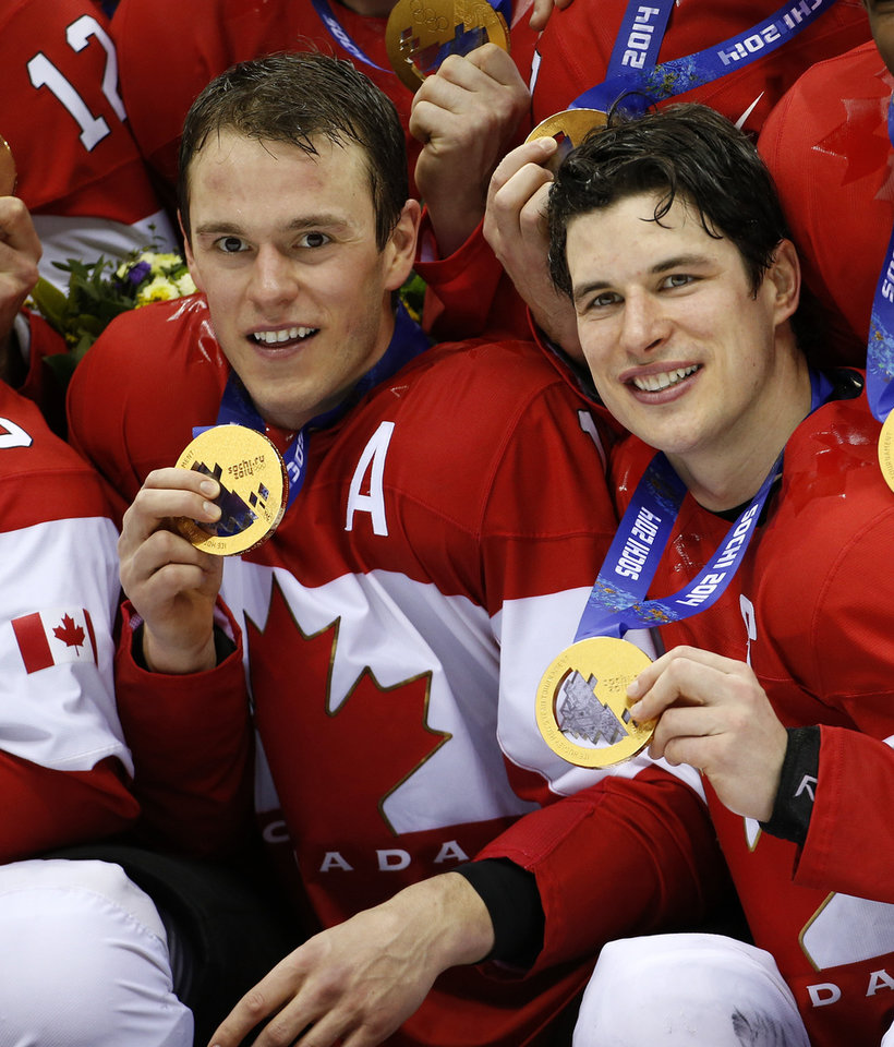 Photo - Canada forwards Jonathan Towes, left, and Sidney Crosby, right, pose with their medals after beating Sweden 3-0 in the men's ice hockey gold medal game at the 2014 Winter Olympics, Sunday, Feb. 23, 2014, in Sochi, Russia. (AP Photo/Mark Humphrey)