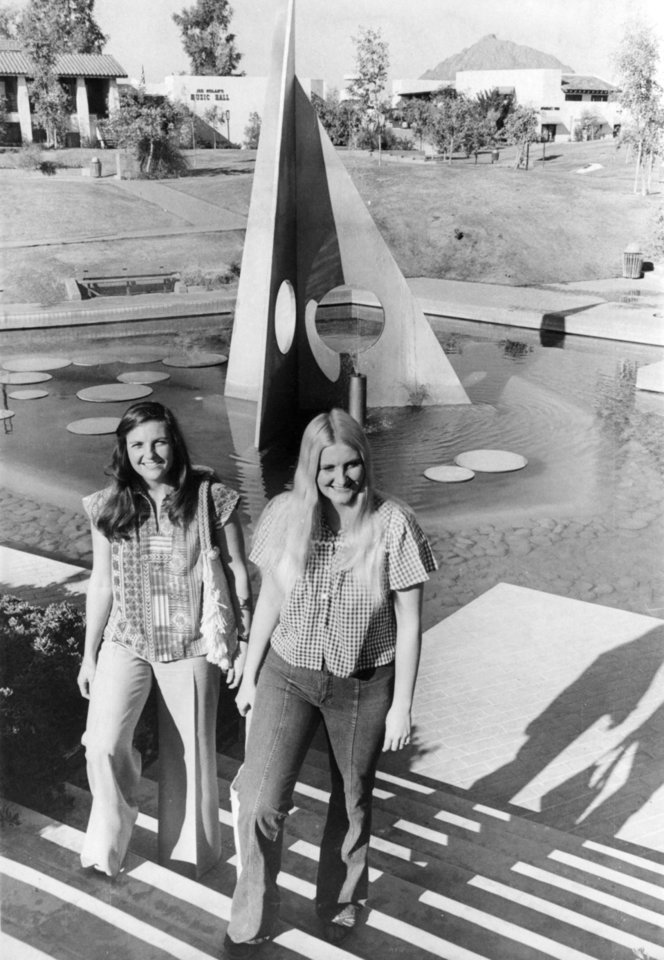 "Photo - FOOTBALL OU UNIVERSITY OF OKLAHOMA FIESTA BOWL 1976 05.jpg: Caption reads "" Mrs. Mike Vaughan, left, and Mrs. Sam Clapham, whose offensive linebacker husbands were practicing, took time to enjoy the weather and the sights. They pose in front of a water sculpture entitled ""Aquarius."" Photo taken by Al McLaughlin. Photo taken 12-23-1976. Photo was published in the Oklahoma City Times on 12-24-1976."