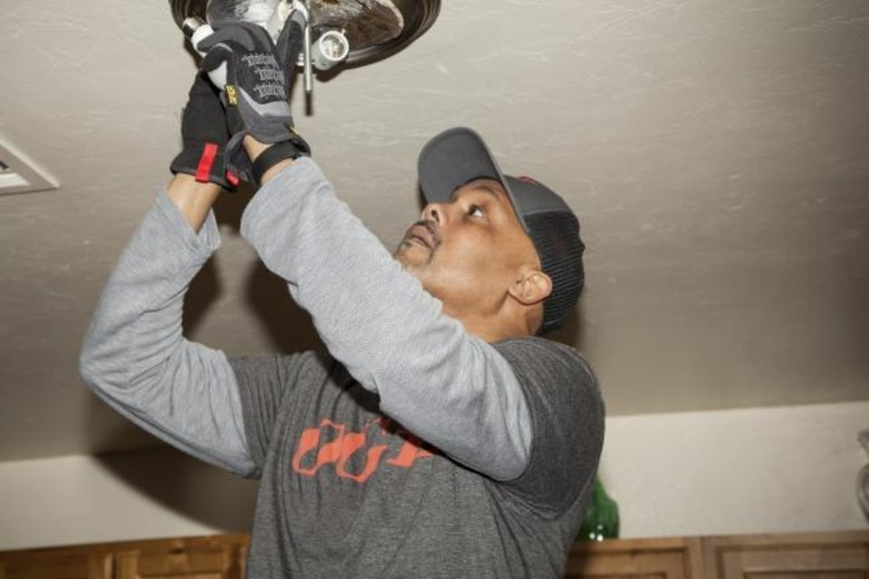 Photo -  Oklahoma Gas and Electric Co. volunteer Kevin Maxwell installs energy saving LED bulbs in a light fixture inside a resident's home at the Mount Olive Senior Cottages development in northeast Oklahoma City on Monday.