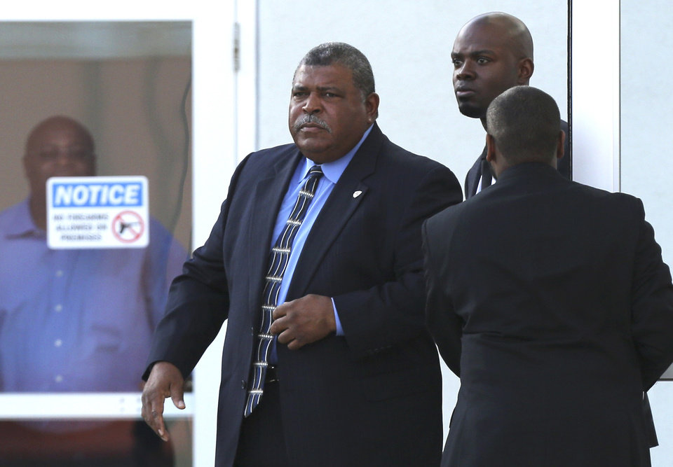 Photo - Kansas City Chiefs head coach Romeo Crennel, left, leaves a memorial service for Kansas City Chiefs' Jovan Belcher at the Landmark International Deliverance and Worship Center Wednesday, Dec. 5, 2012 in Kansas City, Mo. Belcher shot his girlfriend, Kasandra Perkins, at their home Saturday morning before driving to Arrowhead Stadium and turning the gun on himself.  (AP Photo/Ed Zurga)