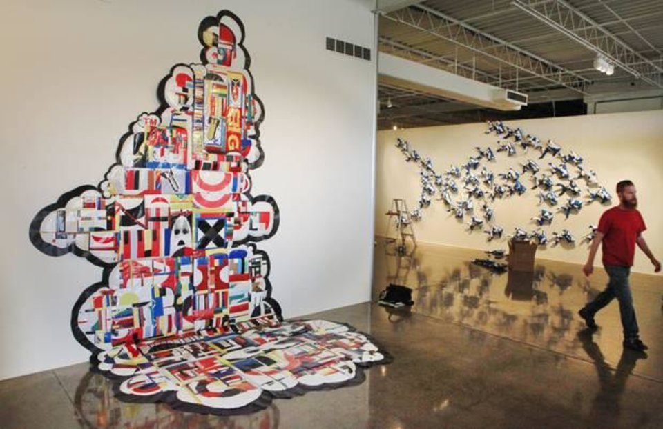 """Photo -  Dallas-based artist Jason Willaford creates abstract artwork by sewing together pieces of vinyl reclaimed from billboards. His pieces """"Info-Nation Overload,"""" left,"""" and """"In Business for Small Business"""" are featured in his exhibit """"Vinyl Exposed"""" at Oklahoma Contemporary Arts Center."""