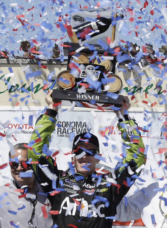 Photo - Carl Edwards holds up his trophy after winning the NASCAR Sprint Cup Series auto race Sunday, June 22, 2014, in Sonoma, Calif. Edwards won the race and Jeff Gordon finished second. (AP Photo/Eric Risberg)