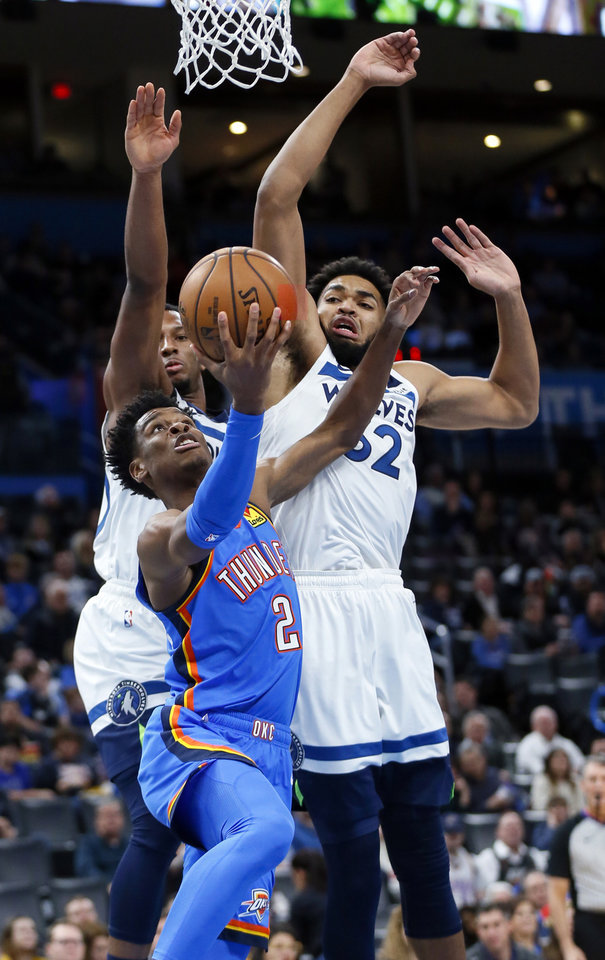 Photo - Oklahoma City's Shai Gilgeous-Alexander (2) shoots in front of Minnesota's Josh Okogie (20), left, and Karl-Anthony Towns (32) during an NBA basketball game between the Minnesota Timberwolves and the Oklahoma City Thunder at Chesapeake Energy Arena in Oklahoma City, Friday, Dec. 6, 2019. [Nate Billings/The Oklahoman]