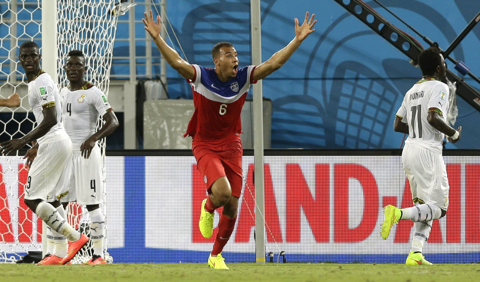 Photo - United States' John Brooks, centre, celebrates after scoring his side's second goal during the group G World Cup soccer match between Ghana and the United States at the Arena das Dunas in Natal, Brazil, Monday, June 16, 2014. The United States won the match 2-1. (AP Photo/Ricardo Mazalan)