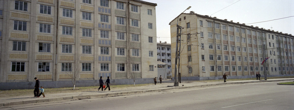 In this April 10, 2012 photo, North Korean pedestrians walk along a street past apartment blocks in central Pyongyang. (AP Photo/David Guttenfelder)