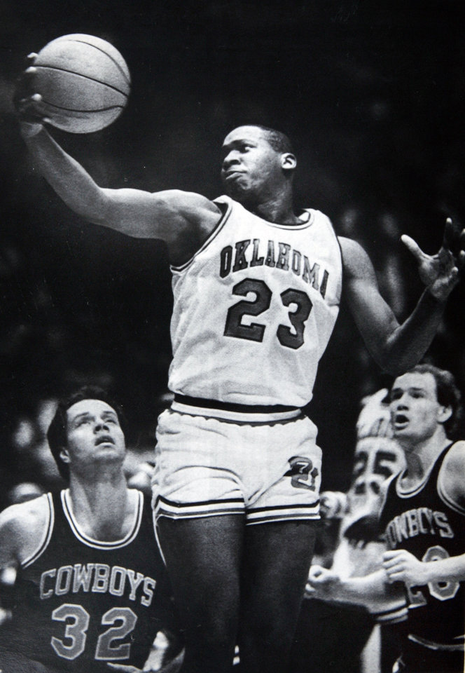 Photo - Former OU basketball player Wayman Tisdale. Norman, Okla., March 5-GRABS THE PASS--Oklahoma center Wayman Tisdale, 23, grabs a pass as Oklahoma State defenders John Nielson, 32, and Bill Self, 20, watch during first half action Tuesday night in Norman, Okla. The fourth ranked Sooners defeated the Cowboys 116-91 in the first round of the Big Eight basketball tournament. (AP LaserPhoto) stf/David Longstreath Photo taken 3/5/1985, published 3/21/1985 in The Daily Oklahoman. ORG XMIT: KOD
