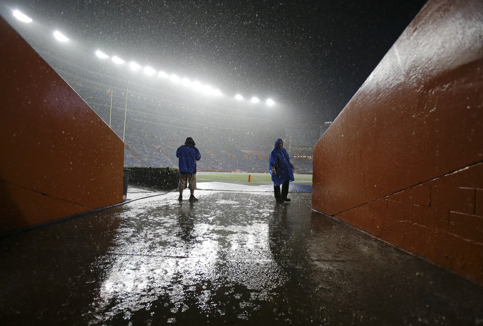 Photo - Rain pours down on the field at Ben Hill Griffin stadium as a weather delay continues to hold up the start of an NCAA college football game between Florida and Idaho in Gainesville, Fla., Saturday, Aug. 30, 2014. (AP Photo/John Raoux)