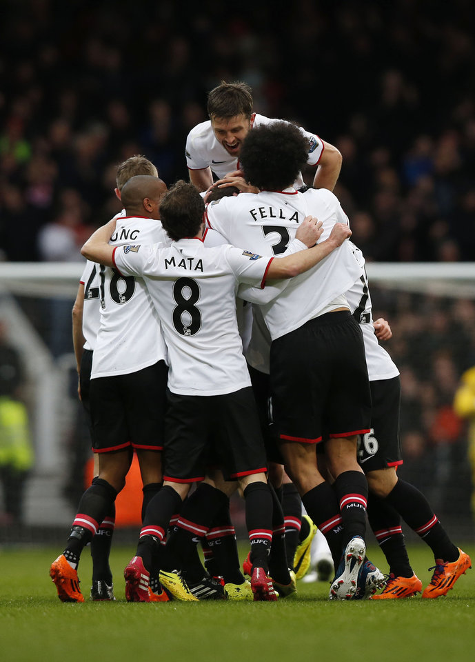 Photo - Manchester United's players celebrate Wayne Rooney's goal against West Ham United during their English Premier League soccer match at Upton Park, London, Saturday, March 22, 2014. (AP Photo/Sang Tan)
