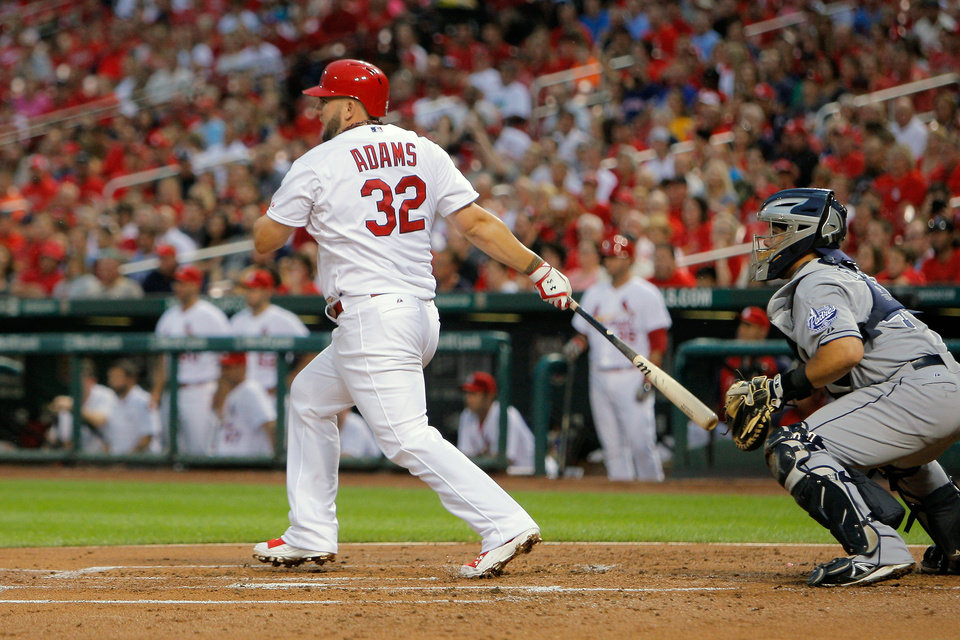 Photo - St. Louis Cardinals' Matt Adams follows through on a RBI single during the first inning of a baseball game against the San Diego Padres Friday, Aug. 15, 2014, in St. Louis. (AP Photo/Scott Kane)
