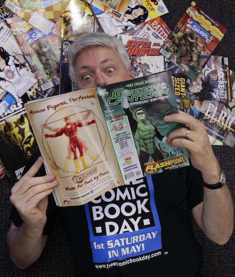 "Joe Field reads a ""Green Lantern"" comic book in his Flying Colors Comics shop in Concord, Calif., before the 10th national Free Comic Book Day in 2011. Field, who created the annual Free Comic Book Day, is the president of ComicsPRO. AP photo <strong>Ben Margot</strong>"