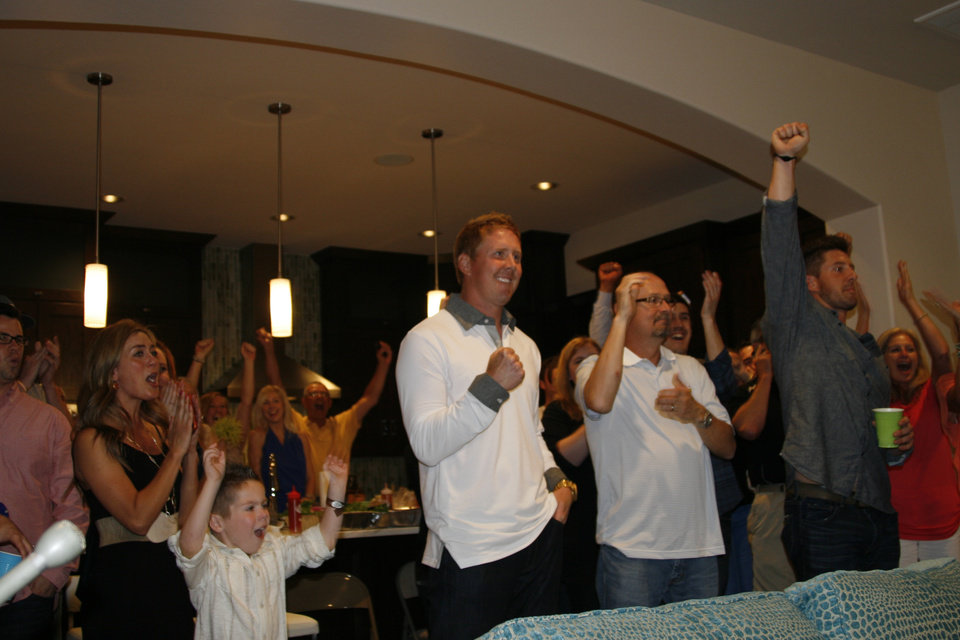 Photo - Former OSU quarterback Brandon Weeden, center, celebrates his NFL Draft selection with friends and family at his parents' home in Edmond. PHOTO BY GINA MIZELL, THE OKLAHOMAN