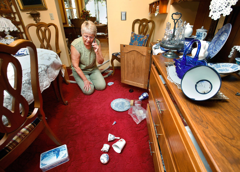 Photo - Mary Reneau talks with her husband on the telephone while she looks at the floor of her dining room, now littered with broken china, glassware and other sentimental keepsakes that were damaged when  tossed to the floor during an earthquake in the early morning hours of Saturday, Nov. 5. , 2011.  Doors of her furniture flew open and drawers were edged slightly open during the quake.  Mary and her husband, Joseph were awakened around 2:15 a.m. when their house shook and items began falling off the walls and form shelves and cabinets inside their two-story brick ranch-style  home in rural Lincoln County, about  six miles northwest of Prague.  Austin Holland, a seismologist with the Oklahoma Geological Survey, placed the quake's epicenter within two to three miles of the Reneau home.  The Reneaus have lived in their house for 25 years. Photo by Jim Beckel, The Oklahoman  ORG XMIT: KOD