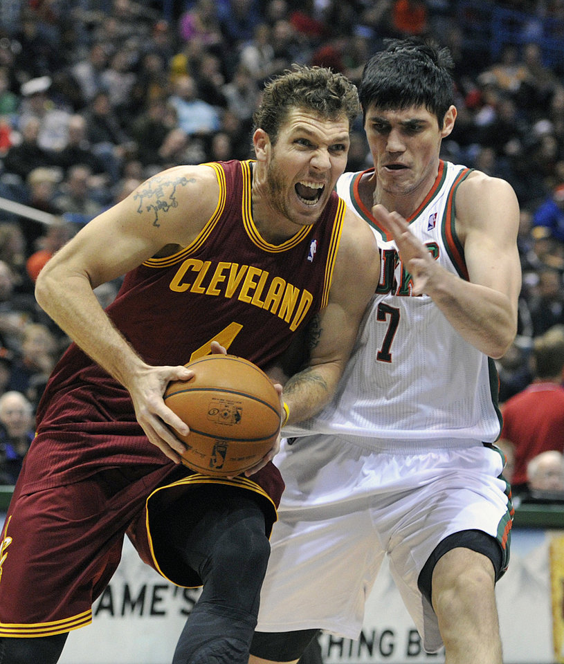 Cleveland Cavaliers' Luke Walton (4) drives to the basket around Milwaukee Bucks' Ersan Ilyasova (7) during the first half of an NBA basketball game Saturday, Dec. 22, 2012, in Milwaukee. (AP Photo/Jim Prisching)