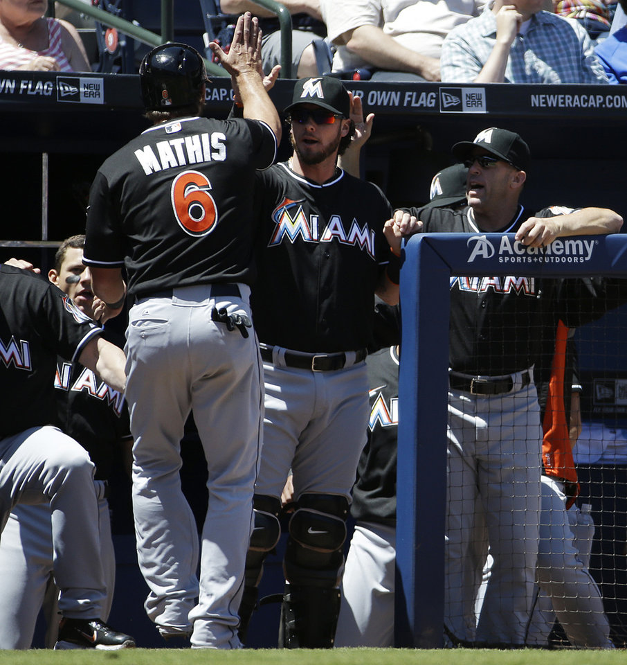 Photo - Miami Marlins' Jeff Mathis, left, is high-fived by teammate Jarrod Saltalamacchia after scoring off a double by Giancarlo Stanton in the sixth inning of a baseball game against the Atlanta Braves, Wednesday, April 23, 2014, in Atlanta. (AP Photo/David Goldman)
