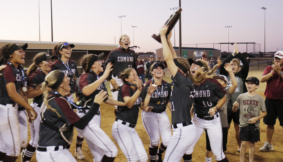 Photo - Edmond players jump with the trophy during the 6A Fast Pitch Championship game between Edmond Memorial and Owasso at the Ball Fields at Firelake in Shawnee, Saturday, October 19, 2019. [Doug Hoke/The Oklahoman]