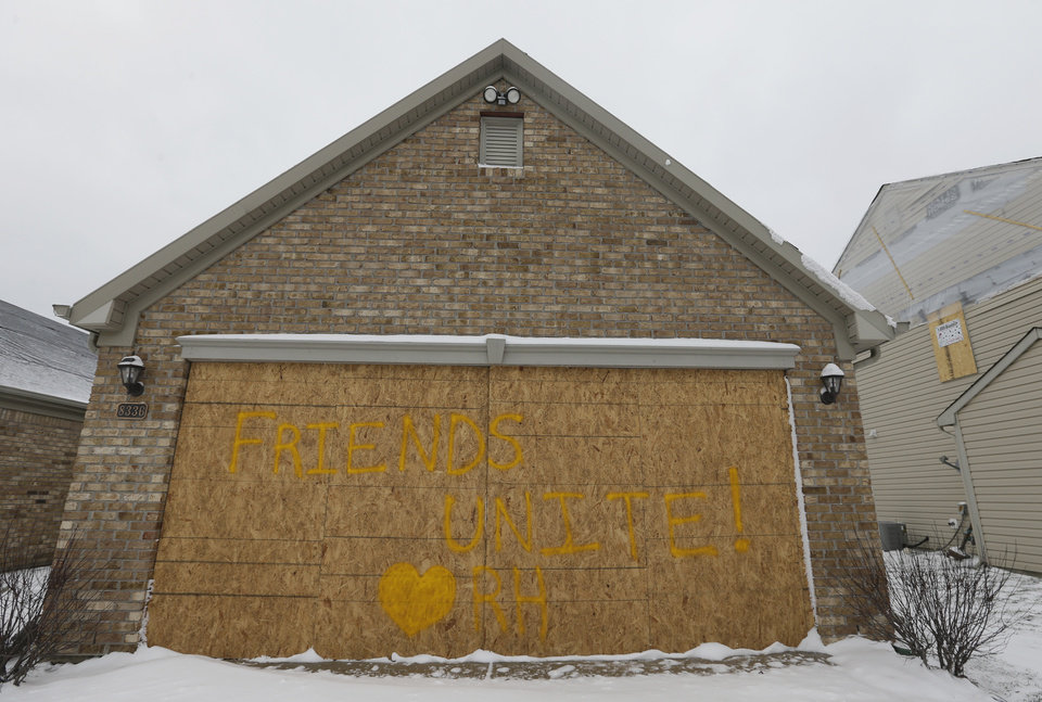 A home owner posted a noted on their bordered up garage in the Richmond Hills neighborhood that was damaged by an explosion on Nov. 10, 2012, is seen Friday, Dec. 21, 2012, in Indianapolis. The massive explosion sparked a huge fire and killed two people in Indianapolis. Prosecutors have charged a homeowner, her boyfriend and his brother with murder after causing the massive house explosion. (AP Photo/Darron Cummings)