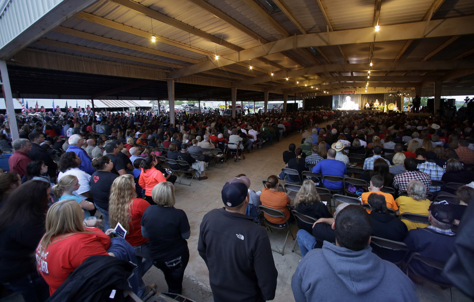 Photo - Thousands of people gather outside and under the roof of a pavilion for a memorial service, Thursday, April 17, 2014, in West, Texas. The service honored those killed by a fertilizer plant explosion one year ago. Fifteen people were killed, including 12 volunteer firefighters and others responding to the fire, and more than 200 were injured. (AP Photo/Tony Gutierrez)