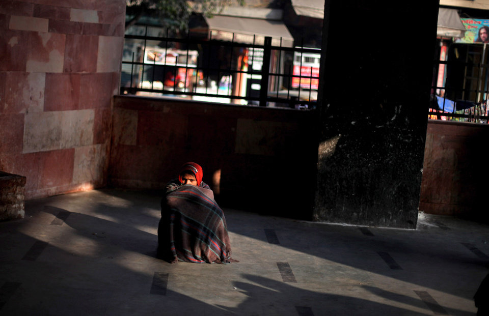 An Indian woman sits wrapped in a blanket at a railway station on a cold morning in New Delhi, India, Wednesday, Jan. 9, 2013. North India continues to face below average weather conditions with dense fog affecting flights and trains. More than 100 people have died of exposure as northern India deals with historically cold temperatures. (AP Photo/Altaf Qadri)