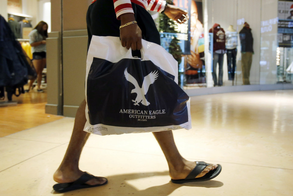 Photo - In this Thursday, Dec. 20, 2012 photo, a shopper carries a bag at the Dolphin Mall in Miami. A last-minute surge in spending helped many major U.S. retailers report better-than-expected sales in December, a relief for stores that make up to 40 percent of annual revenue during the holiday period. (AP Photo/Alan Diaz)