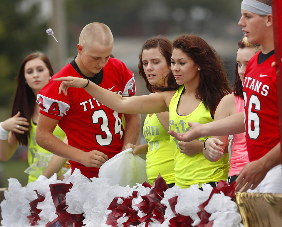 Pom squad members throw candy as they ride on their float. Carl Albert High School is celebrating its 50th birthday this year and students and alumni participated in homecoming week activities, including a two-mile long parade before the football game on Friday, Oct. 12, 2012. Photo by Jim Beckel, The Oklahoman