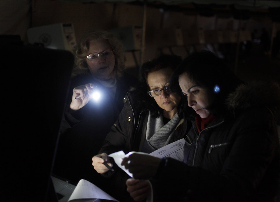 Photo - Poll workers Eva Prenga, right, Roxanne Blancero, center, and Carole Sevchuk try to start an optical scanner voting machine in the cold and dark at a polling station in a tent in the Midland Beach section of Staten Island, New York, Tuesday, Nov. 6, 2012. The original polling site, a school, was damaged by Superstorm Sandy. (AP Photo/Seth Wenig) ORG XMIT: NYSW106