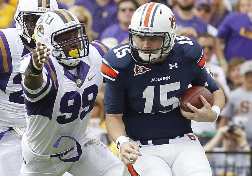 Photo -   FILE - In this Oct. 22, 2011, file photo, LSU defensive end Sam Montgomery (99) reaches for Auburn quarterback Clint Moseley (15) during the first of an NCAA college football game in Baton Rouge, La., Saturday, Oct. 22, 2011. (AP Photo/Bill Haber, File)