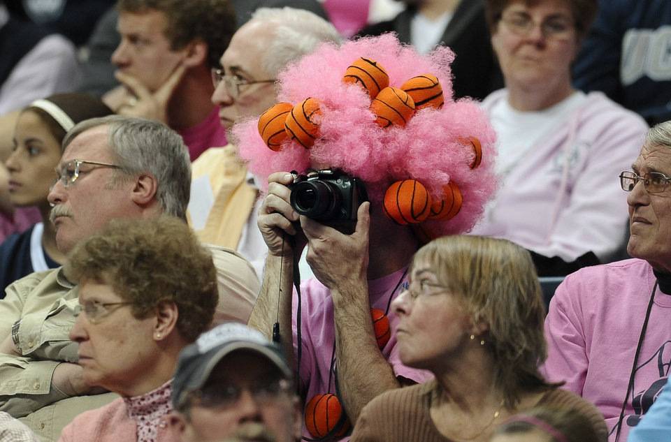 Photo - Sporting a pink wig, Connecticut fan Danny Karkowski takes photos of the team during the second half of an NCAA women's college basketball game against Louisville, Sunday, Feb. 9, 2014, in Storrs, Conn. Connecticut won 81-64. (AP Photo/Jessica Hill)