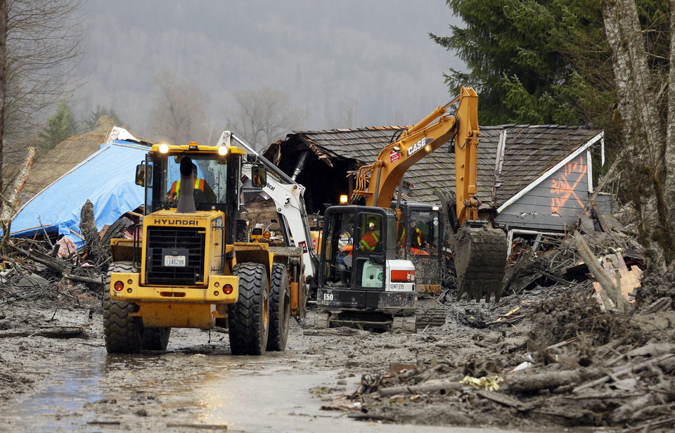 Photo - Workers using heavy equipment work to clear debris Tuesday, March 25, 2014, from Washington Highway 530 on the western edge of the  massive mudslide that struck near Arlington, Wash., Saturday, killing at least 14 people and leaving dozens missing. (AP Photo/Ted S. Warren, Pool)