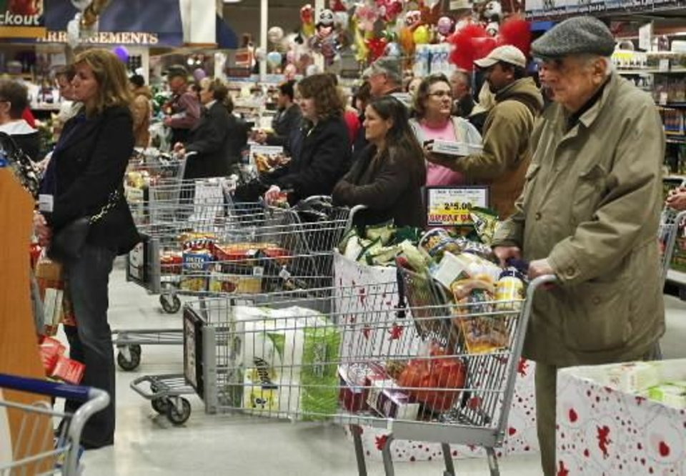 Photo - Customers wait in line at an Oklahoma City grocery store today. Many Oklahomans stocked up on items in anticipation of Tuesday's expected winter storm. Photo by Chris Landsberger