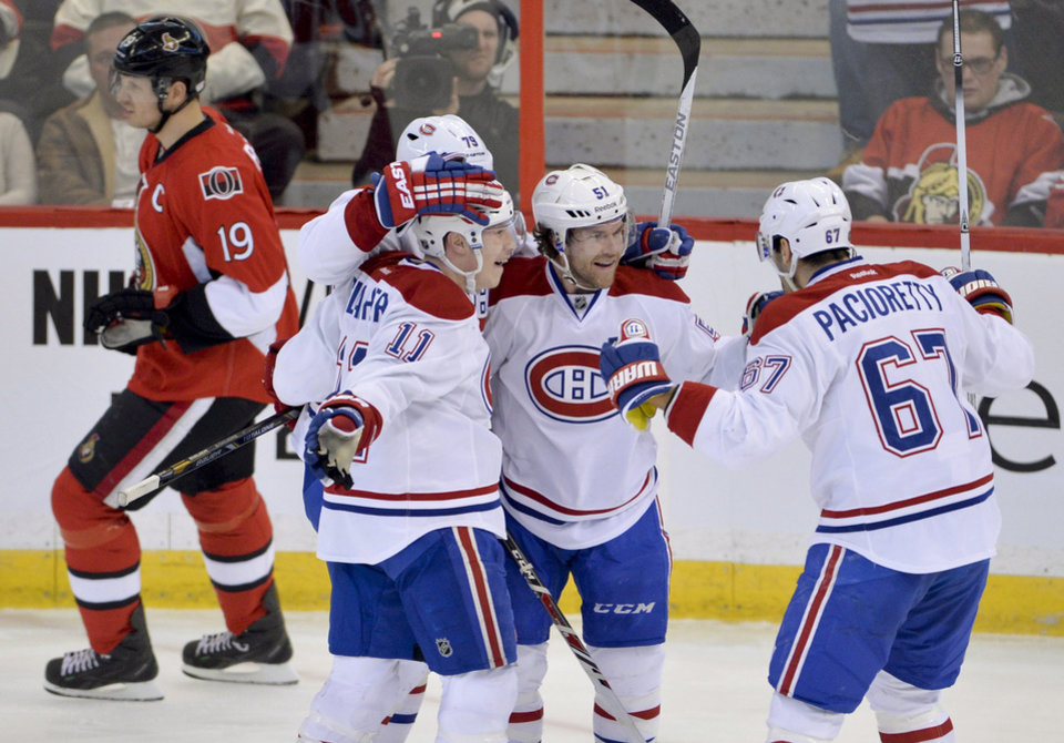 Photo - Ottawa Senators center Jason Spezza skates past Montreal Canadiens' Brendan Gallagher (11), Andrei Markov (79) and Max Pacioretty (67) as they congratulate David Desharnais on his goal during the first period of an NHL hockey game Thursday, Jan. 16, 2014, in Ottawa, Ontario. (AP Photo/The Canadian Press, Adrian Wyld)