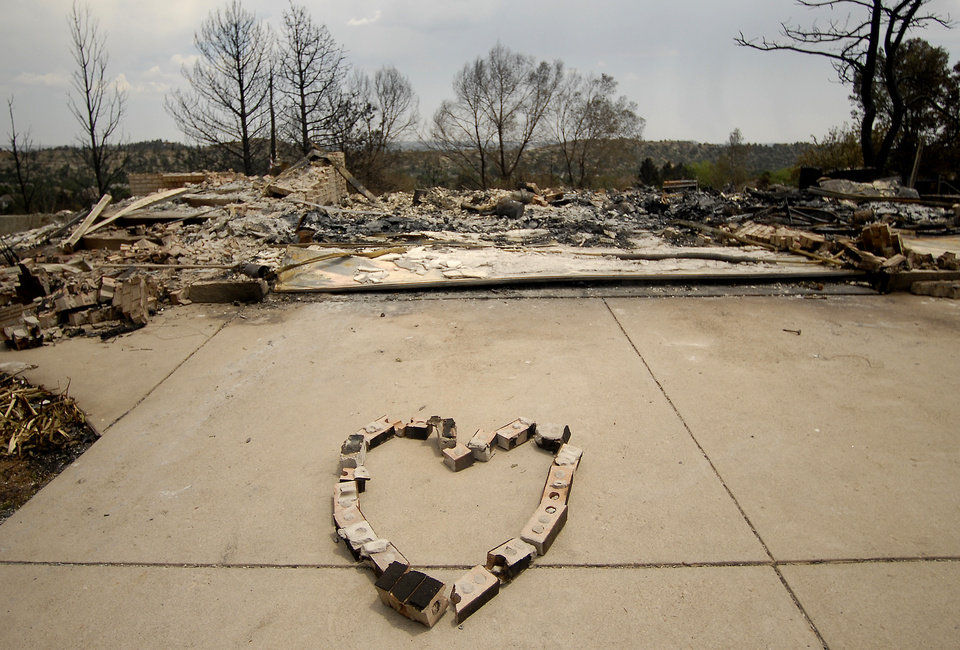 Photo - A heart is made of bricks from a home destroyed by the Waldo Canyon Fire in the Mountain Shadows neighborhood of Colorado Springs, Colo., on Monday, July 2, 2012. So far, the blaze, now 45 percent contained, has damaged or destroyed nearly 350 homes. (AP Photo/Bryan Oller) ORG XMIT: COBO115