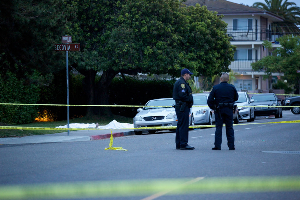 Photo - Police wait at the scene after a drive-by shooting left seven people dead, including the attacker, and others wounded on Friday, May 23, 2014, in Isla Vista, Calif. Alan Shifman an attorney for Hollywood director Peter Rodger, who was an assistant director on The Hunger Games, said the family believes Rodger's son, Elliot Rodger, is responsible for the shooting rampage near the Santa Barbara, California, university campus. Authorities have not confirmed the identity of the shooter. (AP Photo/The News-Press, Peter Vandenbelt)