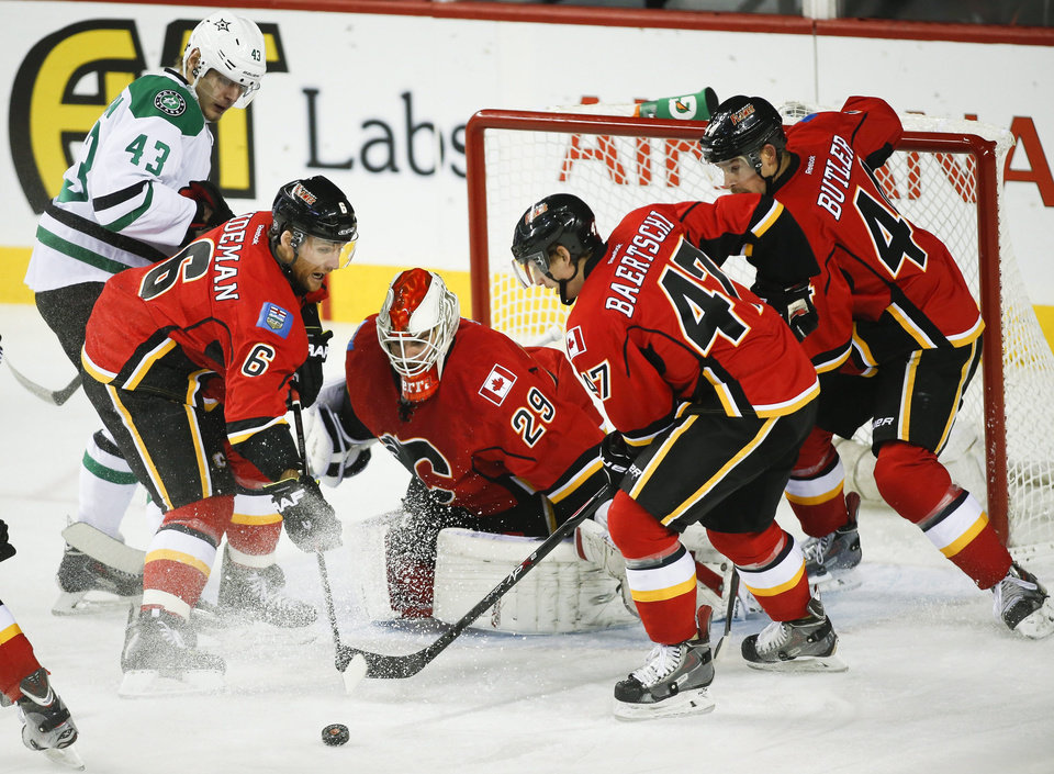 Dallas Stars' Valeri Nichushkin, left, from Russia, looks on as Calgary Flames', from left to right, Dennis Wideman, goalie Reto Berra, from Switzerland, Sven Baertschi, also from Switzerland, and Chris Butler fumble for the puck during first-period NHL hockey game action in Calgary, Alberta., Thursday, Nov. 14, 2013. (AP Photo/The Canadian Press, Jeff McIntosh)