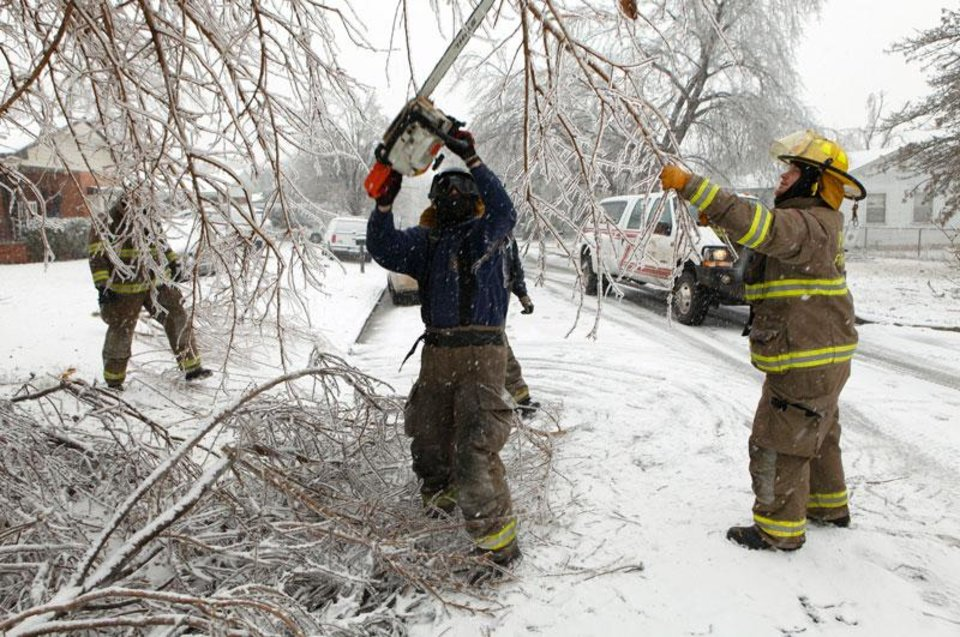 Photo -  Purcell firefighter Jason Benefiel cuts limbs obstructing traffic on Friday, Jan. 29, 2010, in Purcell, Okla., after a winter storm.  Photo by Steve Sisney, The Oklahoman