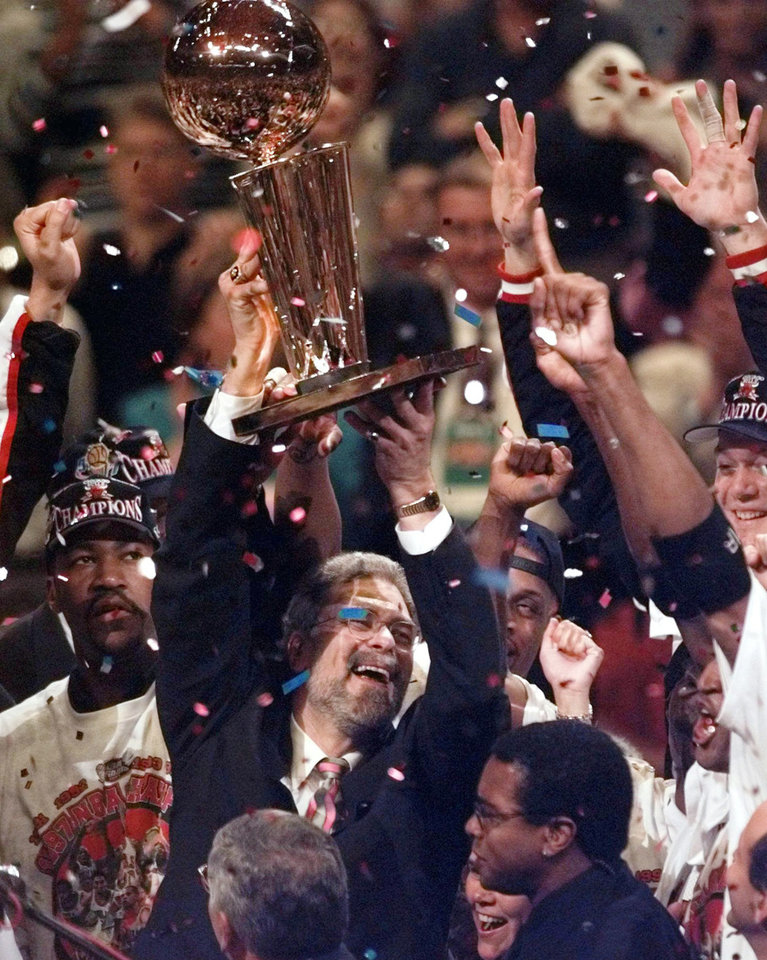 Photo - FILE - In this June 13, 1997 file photo, Chicago Bulls coach Phil Jackson hoists the trophy aloft after the Bulls beat the Utah Jazz 90-86 in Game 6 to win the NBA championship in Chicago. Jackson will be introduced as the newest member of the New York Knicks' front office Tuesday morning, according to a person familiar with the negotiations between the 11-time champion coach and the team.  The person spoke on condition of anonymity on Friday, March 14, 2014, because the Knicks would only confirm that a