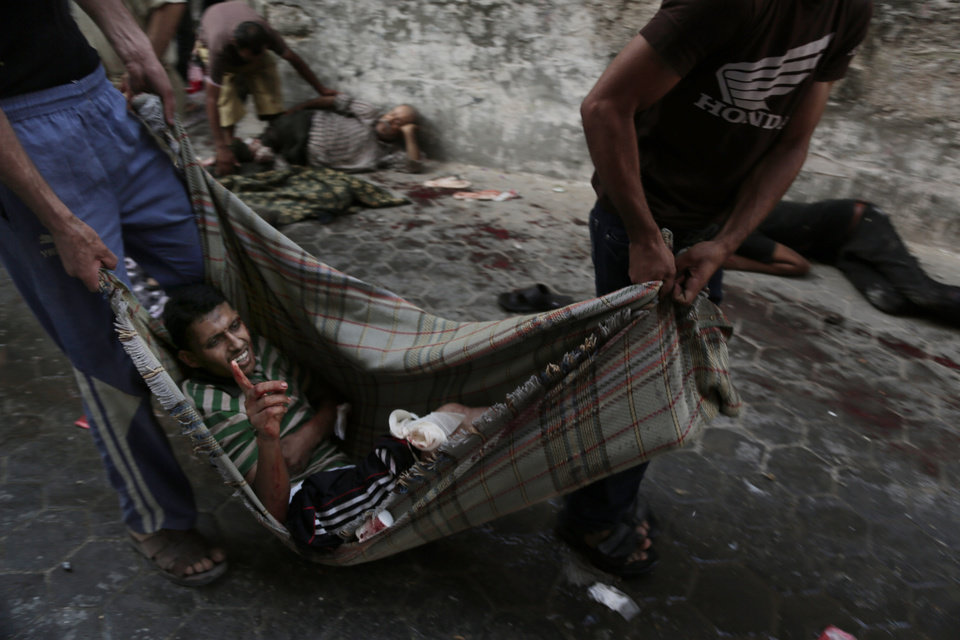 Photo - Palestinians carry an injured man following an Israeli Strike in Shijaiyah neighborhood, eastern Gaza City, Wednesday, July 30, 2014. (AP Photo/Adel Hana)