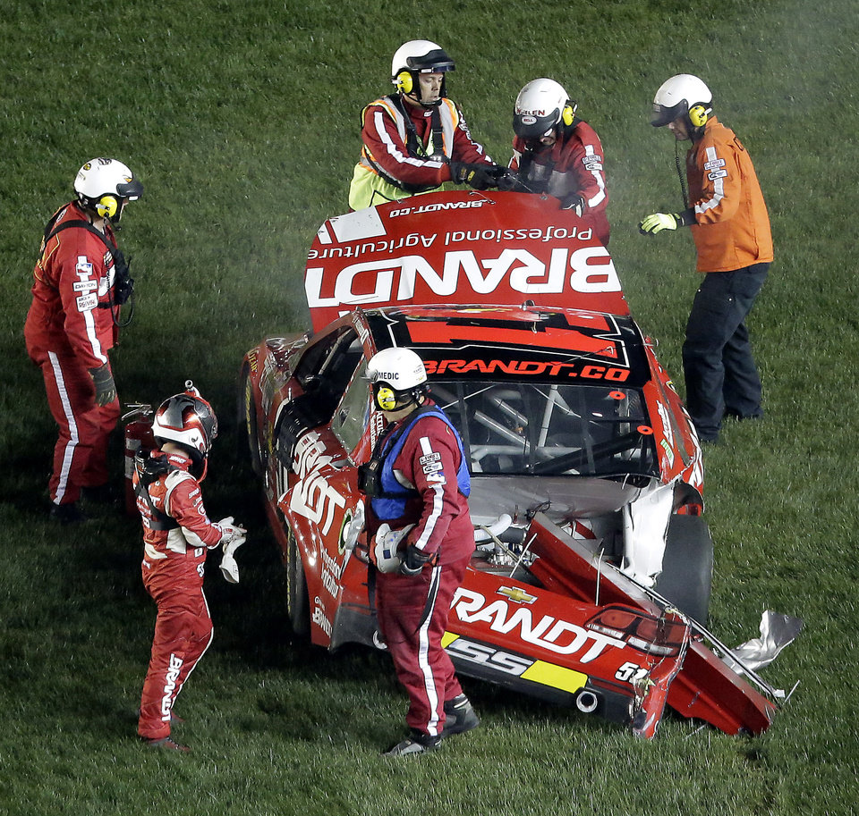 Photo - Justin Allgaier is helped out of his car after crashing during a NASCAR Sprint Cup Series auto race at Kansas Speedway in Kansas City, Kan., Saturday, May 10, 2014. (AP Photo/Charlie Riedel)
