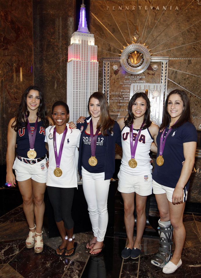 Photo -   CORRECTS SPELLING OF JORDYN - Members of the 2012 US Women's Gymnastics Olympic Team, from left, Aly Raisman, Gabby Douglas, McKayla Maroney, Kyla Ross and Jordyn Wieber pose after ceremonially lighting the Empire State Building, Tuesday, Aug. 14, 2012 in New York. (Photo by Jason DeCrow/Invision/AP)