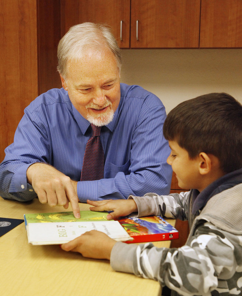 Photo - Steve Hill, chief of staff to Oklahoma City's mayor, works with first grader Jorge Giron, 7, on Thursday at Heronville Elementary School in Oklahoma City. A reading buddies program with students and city employees is one of the programs with roots in a task force of city council members and school officials.  PAUL B. SOUTHERLAND - The Oklahoman