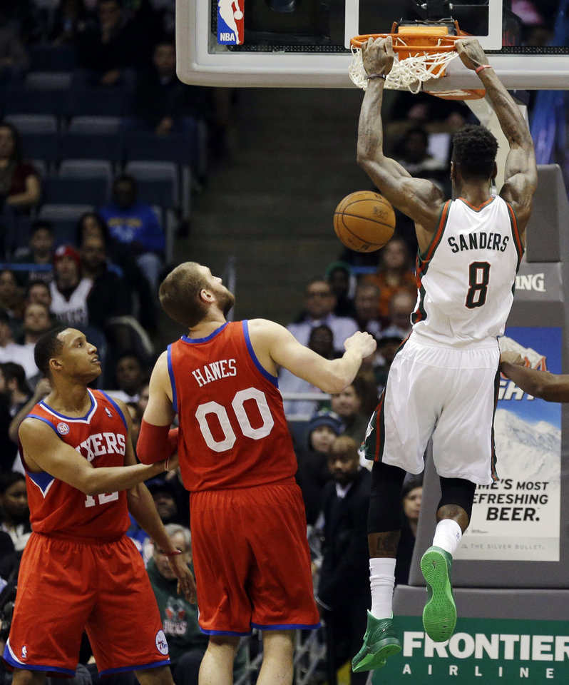 Milwaukee Bucks' Larry Sanders (8) dunks in front of Philadelphia 76ers' Evan Turner, left, and Spencer Hawes (00) during the first half of an NBA basketball game, Tuesday, Jan. 22, 2013, in Milwaukee. (AP Photo/Jeffrey Phelps)
