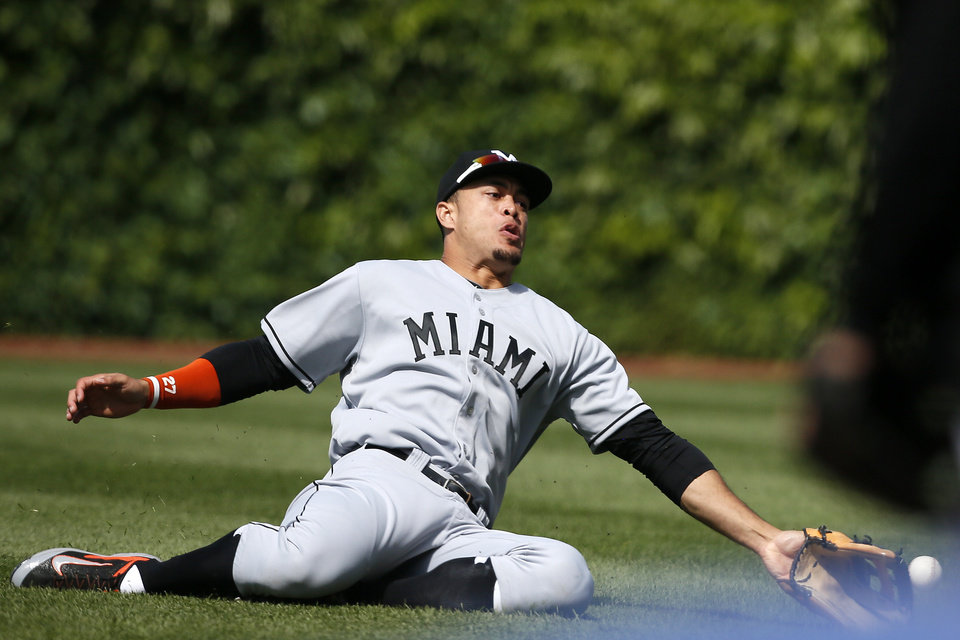 Photo - Miami Marlins right fielder Giancarlo Stanton comes up short of catching a double hit by the Chicago Cubs' Junior Lake during the seventh inning of a baseball game on Sunday, June 8, 2014, in Chicago. (AP Photo/Andrew A. Nelles)