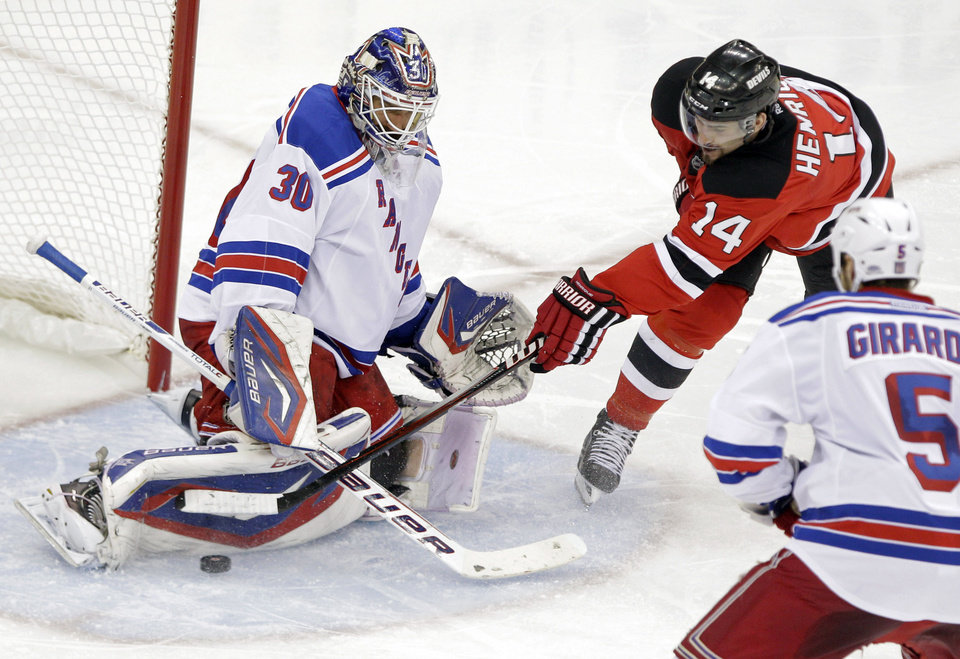 Photo -   New York Rangers goalie Henrik Lundqvist, left, of Sweden stops a shot by New Jersey Devils center Adam Henrique as Rangers defenseman Dan Girardi skates in during the second period of Game 3 of an NHL hockey Stanley Cup Eastern Conference final playoff series, Saturday, May 19, 2012, in Newark, N.J. (AP Photo/Frank Franklin II)